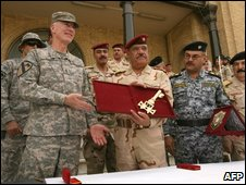 Gen Abboud Qambar receives the symbolic key to the defence ministry from US Gen Daniel Bolger in Baghdad, 29 June