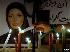 An Iranian, sporting a green ribbon on her arm, lights a candle in front of a picture of Neda Agha-Soltan in Dubai