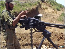 A Pakistani soldier stands with his heavy machine gun on a hill of the Biha valley in upper Swat on June 20, 2009