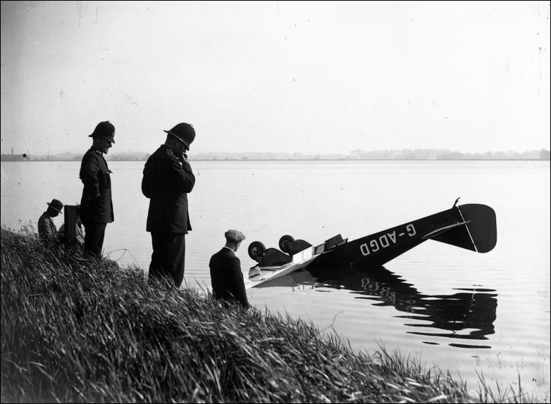 Policemen survey the wreckage of a plane