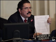 President Manuel Zelaya holds a copy of the OAS resolution