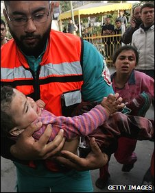 A wounded Palestinian child is carried into the Kamal Adwan hospital after an Israeli air strike on 11 January