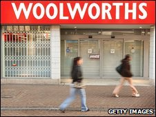 People walk past a boarded-up Woolworths store