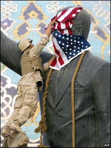 US Marine covering the face of Saddam Hussein's statue with the US flag in Baghdad