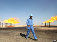 An engineer walking past the chimneys at the Barjisiya oil field