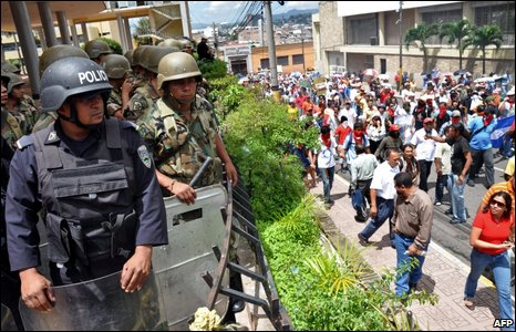Honduran security forces watch as Zelaya supporters march in Tegulcigalpa, 2 July