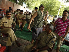 Policemen look on at gays celebrating the court ruling in Delhi