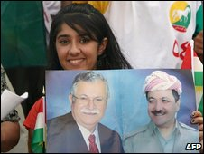 An Iraqi Kurdish woman hold a poster showing Iraqi President Jalal Talabani (L) and Massoud Barzani (R)