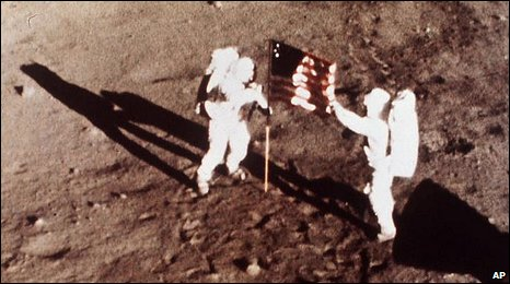 Neil Armstrong and Buzz Aldrin plant the US flag on the surface of the moon
