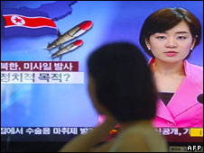 A woman watches a news cast about the launches in Seoul on 4 July