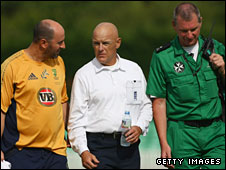 Umpire Jeff Evans (centre) is helped off the field