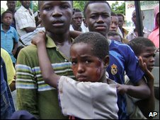 A Somali man carries a boy wounded during mortar shelling, Wednesday, June 17, 2009
