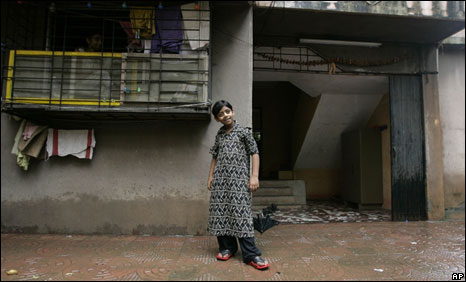 Azharuddin Ismail prepares to pose for a photo outside his newly allocated apartment in central Mumbai on July 4, 2009.