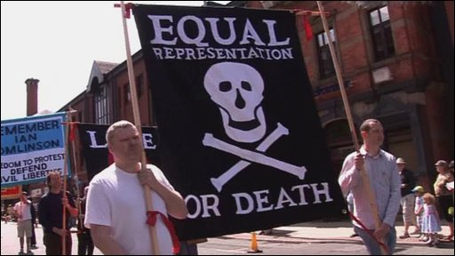 people carrying a banner with skull and crossbones