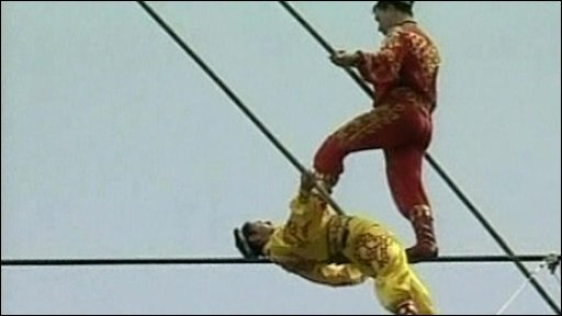 China's 'Prince of tightrope walking' Ahdili passing his pupil on a high wire set 1,607metres above sea level.
