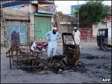 Pakistani local residents look at the wreckage of a destroyed vehicle a day after a suicide bomb attack in Dera Ismail Khan, on May 29, 2009
