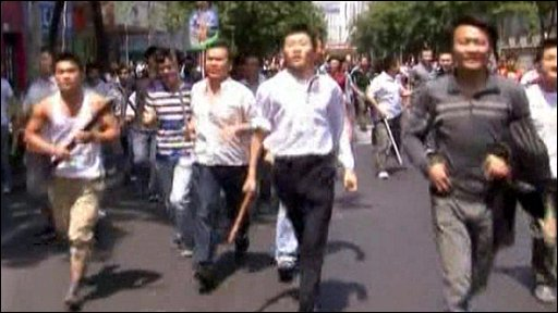 Men carrying baseball bats and sticks