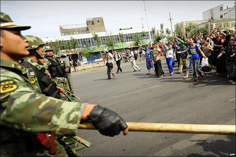 A riot policeman clutches his baton as the he as his colleague face the protestors