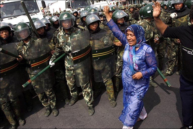 Uigher woman walks, arm raised, in front of ranks of riot police