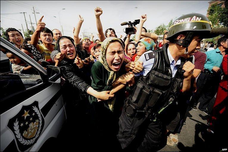 Distraught woman grab at a riot policeman