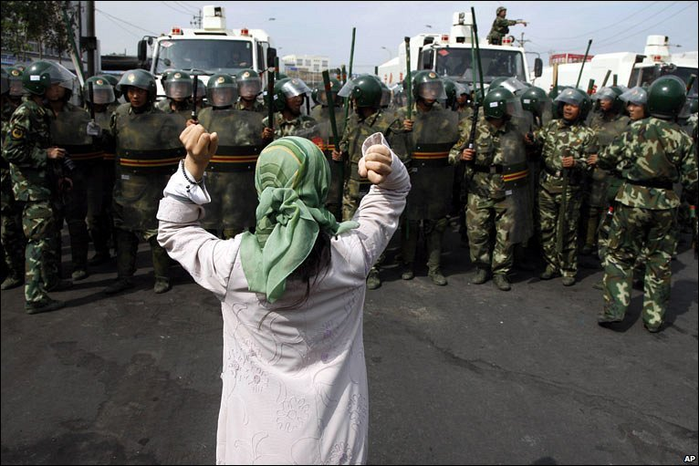 An Uigher woman faces the riot police, both arms raised