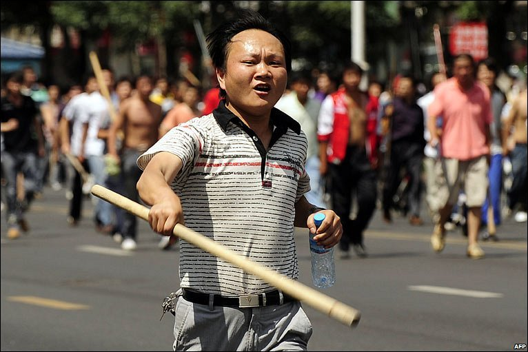 Ethnic Han Chinese man runs through the streets with a large baton