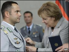 German Chancellor Angela Merkel presents a soldier with the Cross of Honour for Bravery