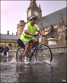 A man cycles through puddles,outside the Houses of Parliament, in London, as a summer storm passes over the capital