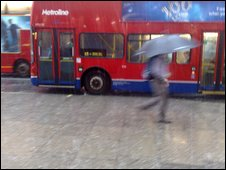 Man running to catch a bus on Oxford street during the downpour
