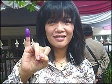 A voter holds up her finger, marked with ink to show she has voted.