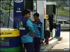 Pakistani petrol station employees wait for vehicles in Islamabad on July 1, 2009.