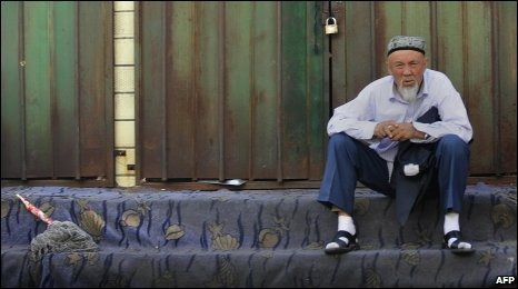 An ethnic Uigur man sits outside shuttered shops in Urumqi