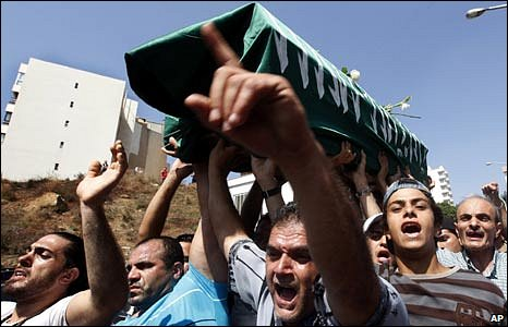 Angry men hold Zeina Miri's coffin, wrapped in a green flag, aloft