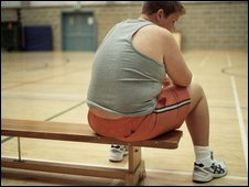 Obese boy sitting on a bench in a gymnasium