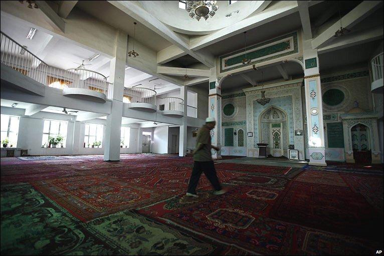 A caretaker walks through an empty mosque in Urumqi