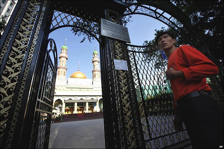 A man walks past a mosque's gates, where the authorities have put up a notice cancelling Friday prayers