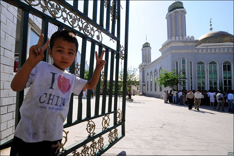 """A child dressed in an """"I love China"""" T-shirt, makes the victory sign to the camera, outside an Urumqi mosque"""