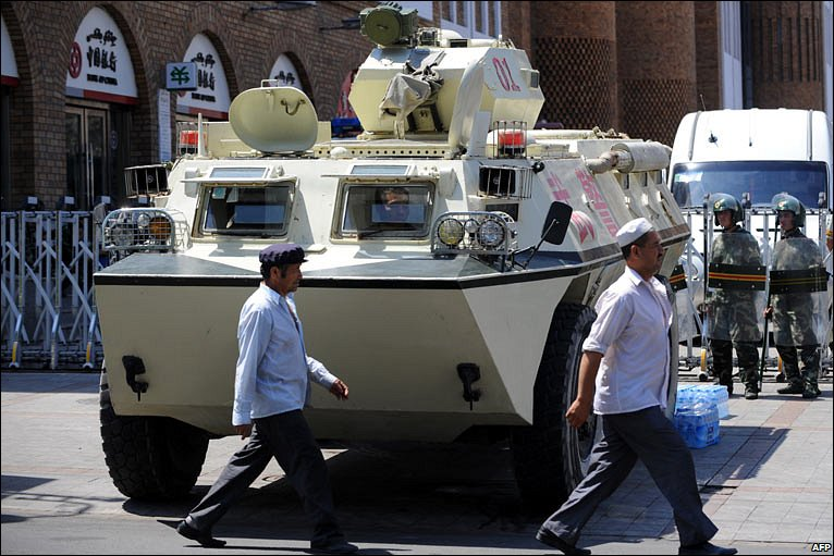 Two Uighur men walk past an armoured vehicle.