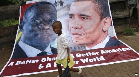 A young girl walks past a banner depicting U.S. President Barack Obama and Ghana President John Atta Mills