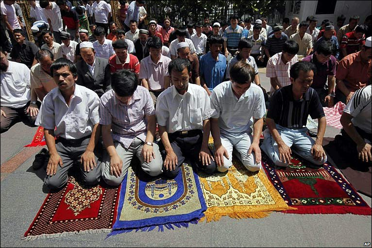Men kneel on brightly-coloured mats in a mosque courtyard