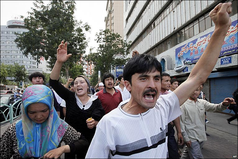 A small group of Uighurs stage a protest, arms raised