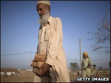 PESHAWAR, PAKISTAN - JULY 06: A Pakistani man, internally displaced from Swat, gathers bricks left over from the construction of a new kitchen at the Yar Hussain UNHCR camp in Chota Lahore on July 6, 2009 in Swabi district