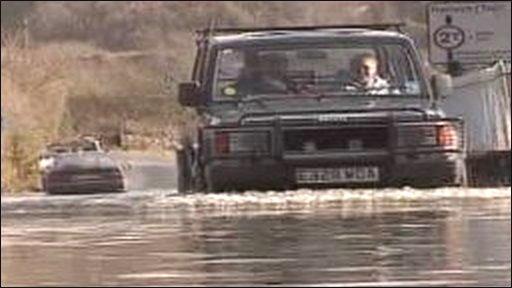 Car drives through flood water