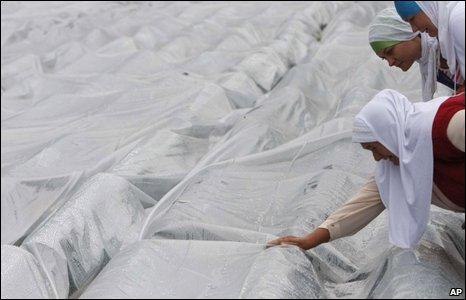 Bosniak Muslim women weep over shrouded coffins at Potocari cemetery outside Srebrenica, 11 July