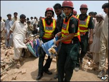 Pakistani rescue workers carry a sack of explosives material found from the rubble of a house after a massive explosion in Mian Channu near Multan, Pakistan on Monday, July 13, 2009.