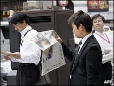 Two smartly-dressed Japanese men read this morning's newspapers in the street