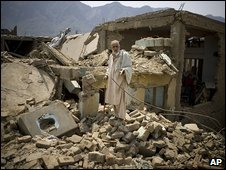 An old man stands in the ruins of his house in Sultanwas, Buner