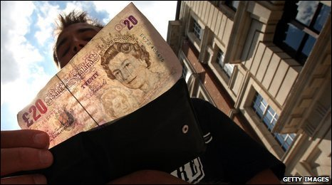 Man holding a £20 note
