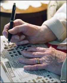 Elderly woman's hands doing cross word