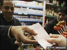 Shopkeeper selling a lottery ticket